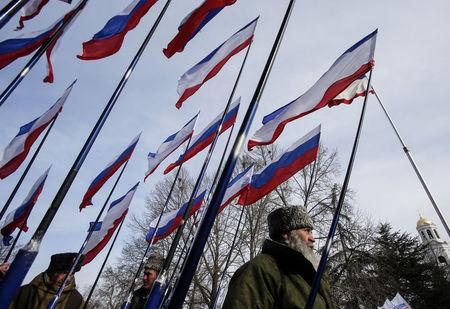 Members of pro-Russian self-defence units hold Russian and Crimean flags during meeting to celebrate first anniversary of Russia's annexation of Crimea in Simferopol