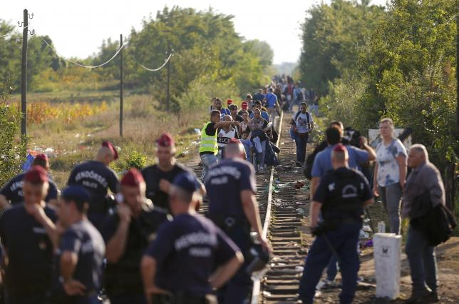 Migrants arrive along rail tracks as Hungarian police officers seal off the border with Serbia, near the Hungarian migrant collection point in Roszke