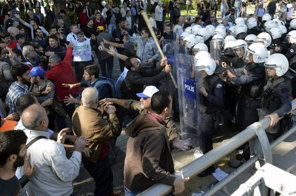 Demonstrators confront riot police following explosions during a peace march in Ankara