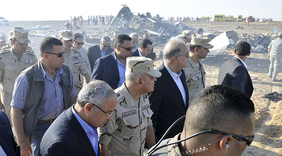 Egypt's Prime Minister Sherif Ismail (C) and Egypt's Defense Minister Sedki Sobhi (2nd L) walk at the site where a Russian airliner crashed in central Sinai near El Arish city, north Egypt, October 31, 2015. The Airbus A321, operated by Russian airline Kogalymavia under the brand name Metrojet, carrying 224 passengers crashed into a mountainous area of Egypt's Sinai peninsula on Saturday shortly after losing radar contact near cruising altitude, killing all aboard. REUTERS/Stringer - RTX1U59A