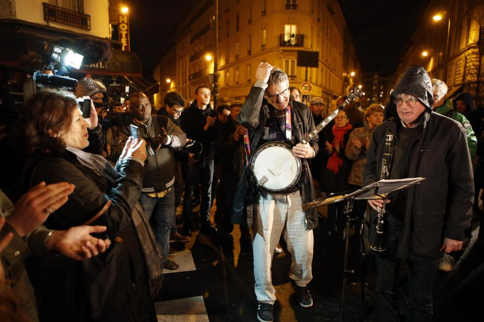 "Jazz musicians acknowledge applause in front of ""The Petit Cambodge"" Restaurant, one of the sites of most deadly of six coordinated extremists attacks, in Paris, France, Friday, Nov. 20, 2015. French artists and cultural figures are calling for people to mark a week since the start of the Paris attacks with an outpouring of ""noise and light"". (AP Photo/Francois Mori)"