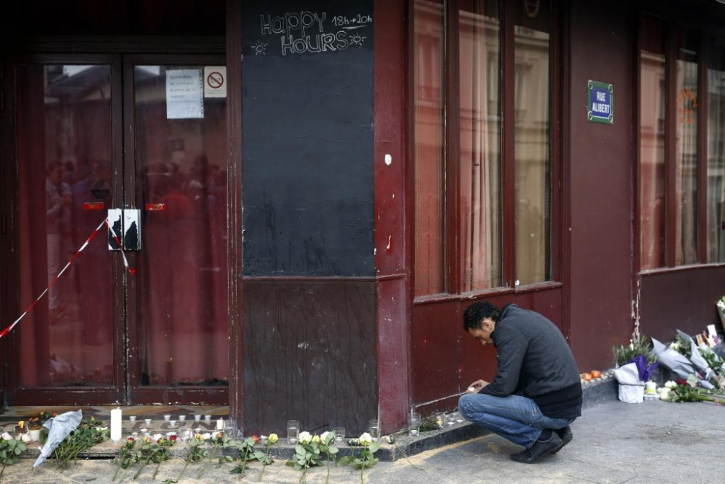 A man places a candle in front of the Carillon cafe in Paris on Nov. 14, 2015, a day after over 120 people were killed in a series of shooting and explosions. (AP Photo/Jerome Delay)