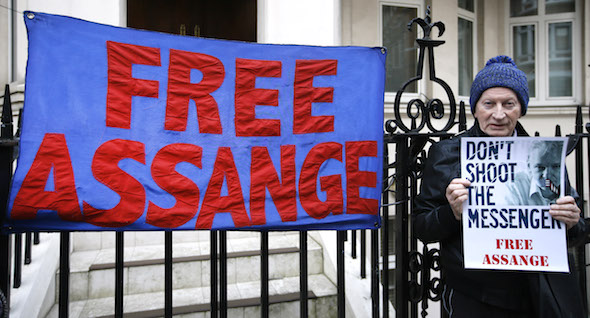 A demonstrator holds a banner outside the Ecuadorean Embassy in London, where Wikileaks founder Julian Assange is staying, Thursday, Feb. 4, 2016. WikiLeaks founder Julian Assange says he will accept arrest by British police if a U.N. working group investigating his claims decides that the three years he has spent inside the Ecuadorean Embassy doesn't amount to illegal detention. (AP Photo/Kirsty Wigglesworth)