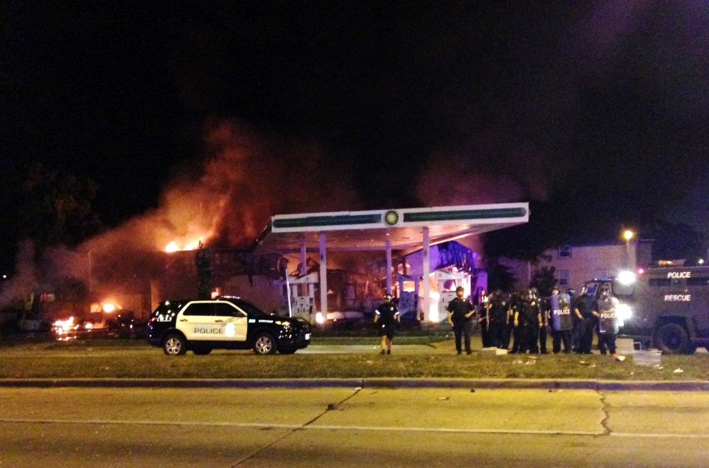 Authorities respond near a burning gas station as dozens of people protest following the fatal shooting of a man in Milwaukee, Saturday, Aug. 13, 2016. A crowd of protesters skirmished with police Saturday night in the Milwaukee neighborhood where an officer shot and killed a man after a traffic stop and foot chase earlier in the day, setting fire to a police car and torching a gas station. (AP Photo/Gretchen Ehlke)