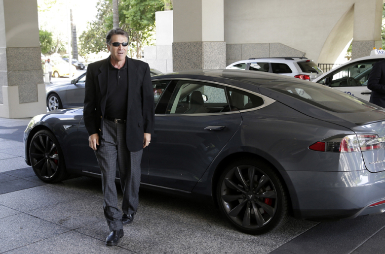File - In this June 10, 2014 file photo, Texas Gov. Rick Perry walks over to talk to reporters after driving up in a Tesla Motors Type S electric car in Sacramento, Calif. Texas and California are two of five states where Tesla Motors is considering building a $5 billion factory to make batteries for a new model of electric car. (AP Photo/Rich Pedroncelli, File)