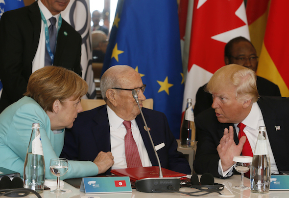 U.S. President Donald Trump, right, and German Chancellor Angela Merkel, left, speak with Tunisian President Beji Caid Essebsi as they attend a round table meeting of G7 leaders and Outreach partners at the Hotel San Domenico during a G7 summit in Taormina, Italy, Saturday, May 27, 2017. Leaders of the G7 wrap up their meeting on Saturday with discussions focused on terrorism, climate and trade. (AP Photo/Domenico Stinellis)