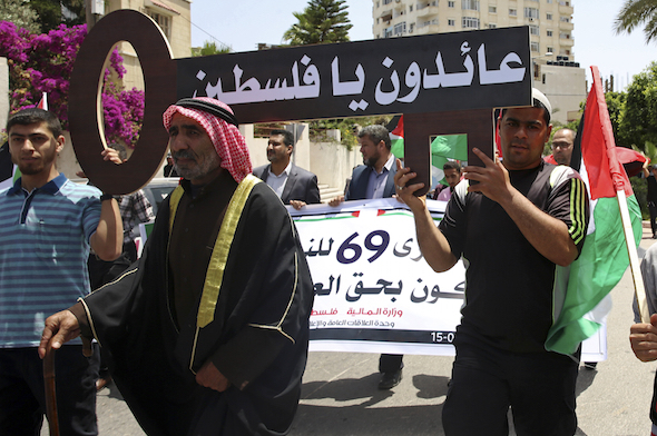 "youths carry home made return's key with Arabic reads ""we will be back to Palestine"" during commemorations of the 69th anniversary of Nakba Day, in front of the offices of the United Nations Special Coordinator for the Middle East Peace Process, in Gaza City, Monday, May 15, 2017. Thousands of Palestinians have marked the anniversary of their uprooting almost seven decades ago with sirens and low-key marches. Hundreds of thousands of Palestinians fled or were driven out in the Mideast war over Israel's 1948 creation. (AP Photo/Adel Hana)"