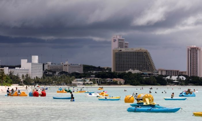 Tourists frolic on the waters overlooking posh hotels in Tumon tourist district. REUTERS/Erik De Castro
