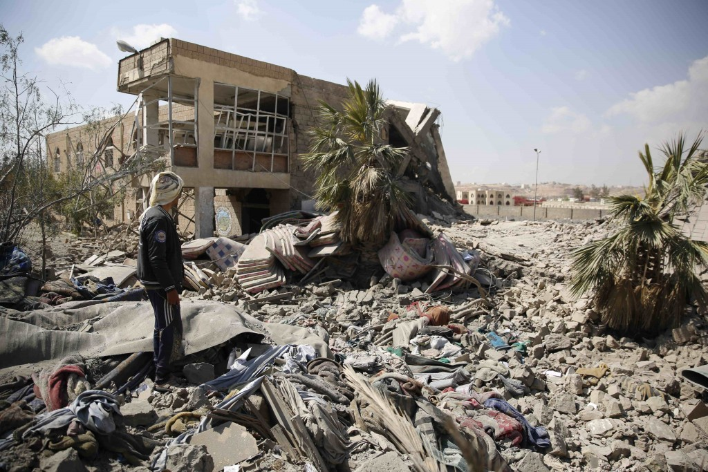 An employee inspects the rubble of the Youth and Sports Ministry's building that was destroyed by Saudi-led airstrikes in Sanaa, Yemen, Sunday, Jan. 17, 2016. (AP Photo/Hani Mohammed)