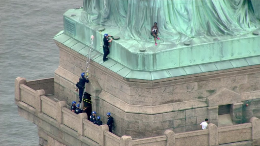 **Embargo New York** A woman has climbed the base of the Statue of Liberty and seven people have been arrested on Liberty Island, all of whom are believed to be protesters, law enforcement sources told CNN.